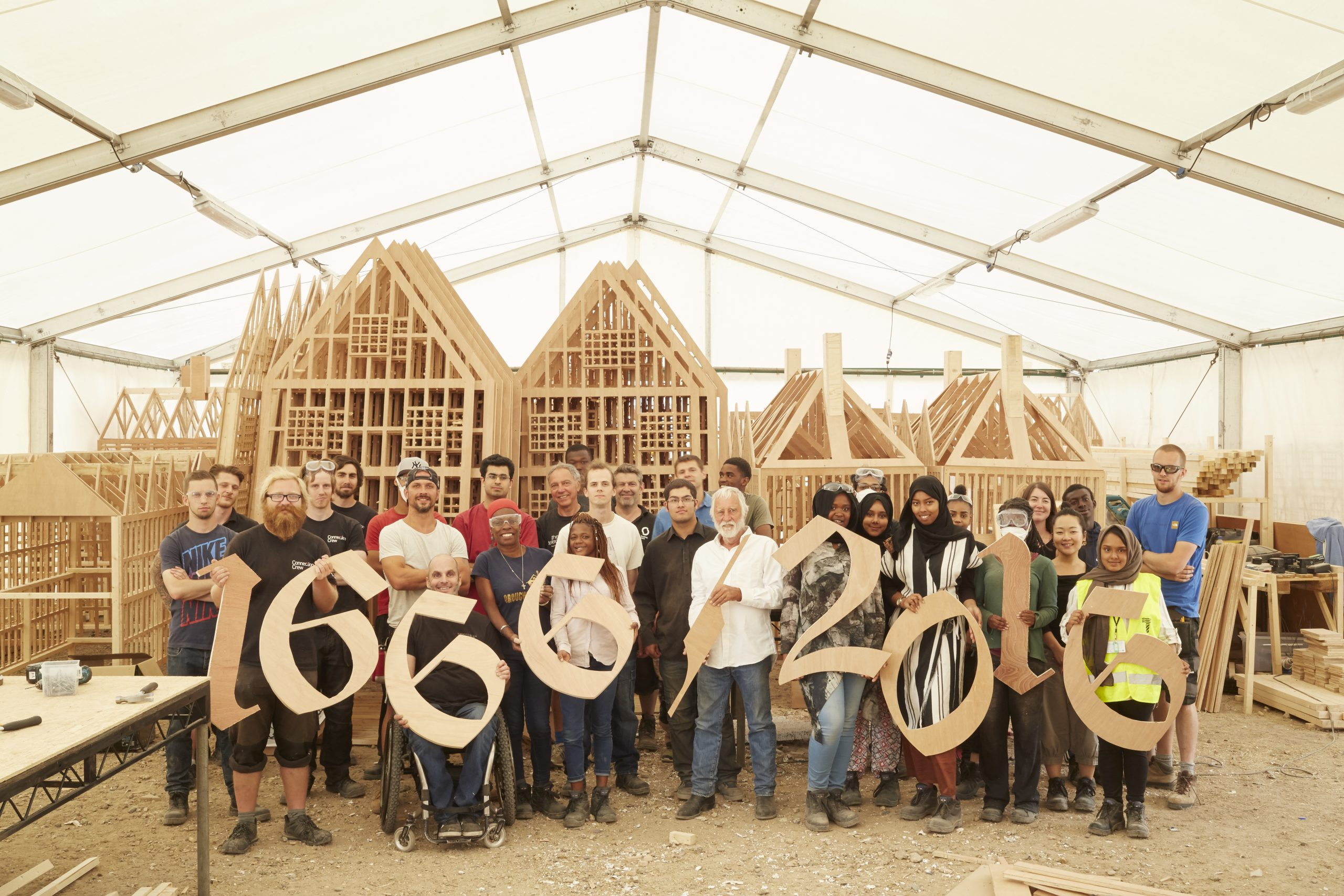 London 1666 participants and artist David Best holding up wooden numbers which say