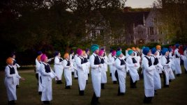 Waiters in multicoloured turbans and black and white uniforms standing in a group in a garden