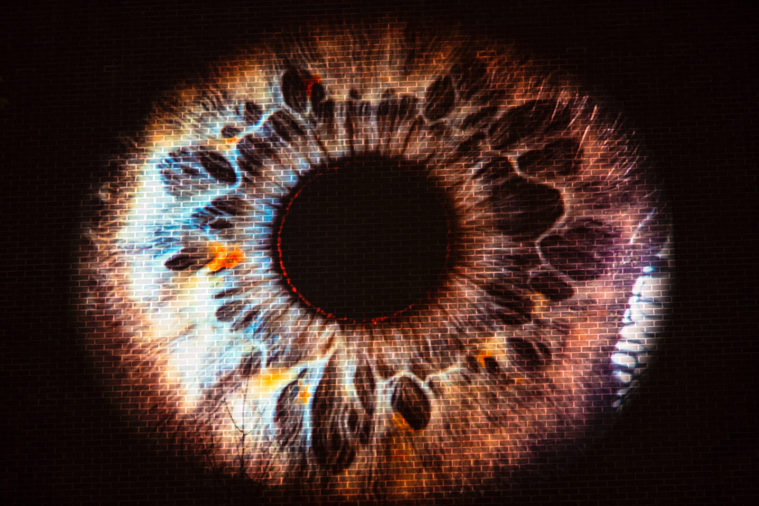 Image of a brown eye projected onto a brick wall