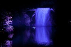 Illuminated purple waterfall with canoes underneath