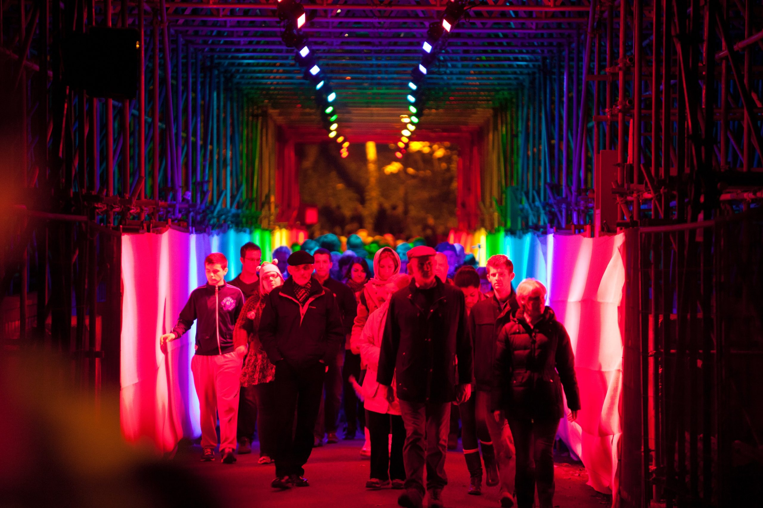 People walking through a square tunnel lit up in rainbow colours