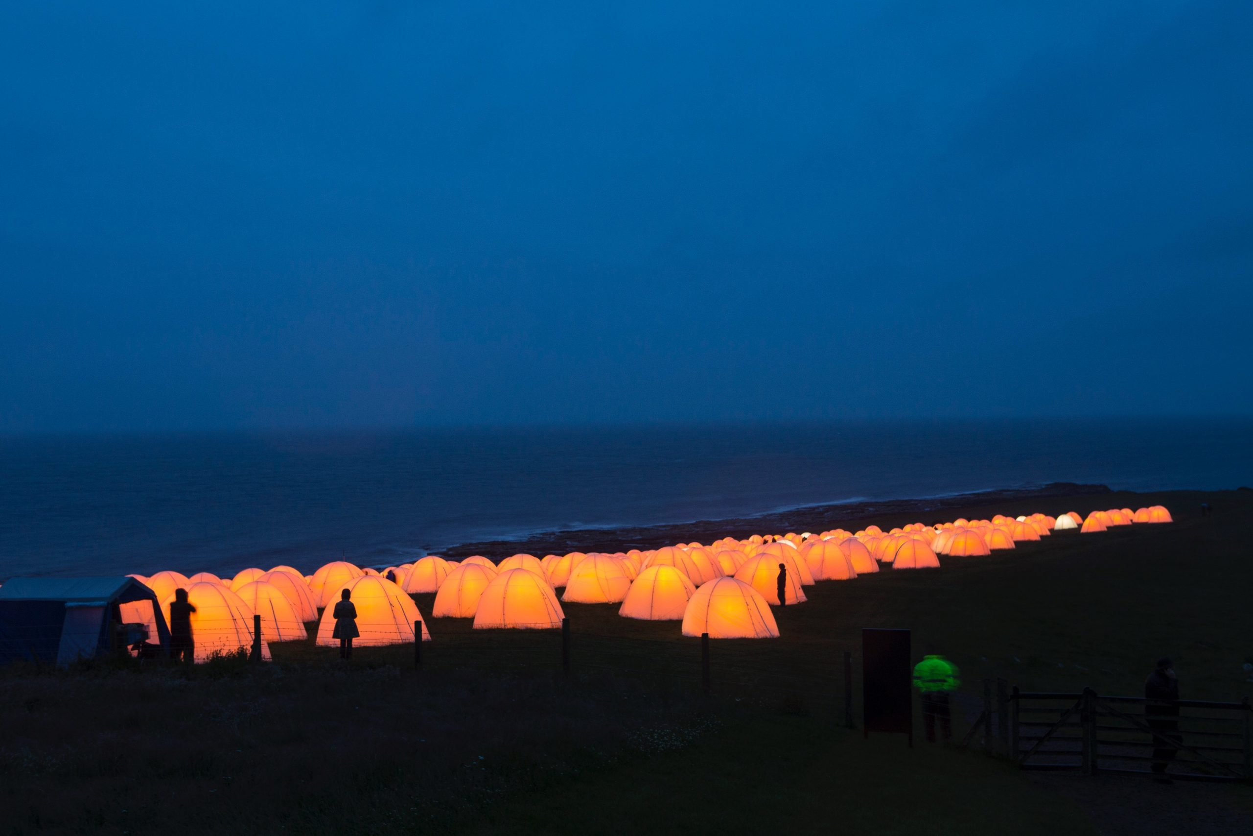Peace camp at Dunstanburgh Castle, Craster, Northumberland. Behind the glowing tents at dusk is the seafront