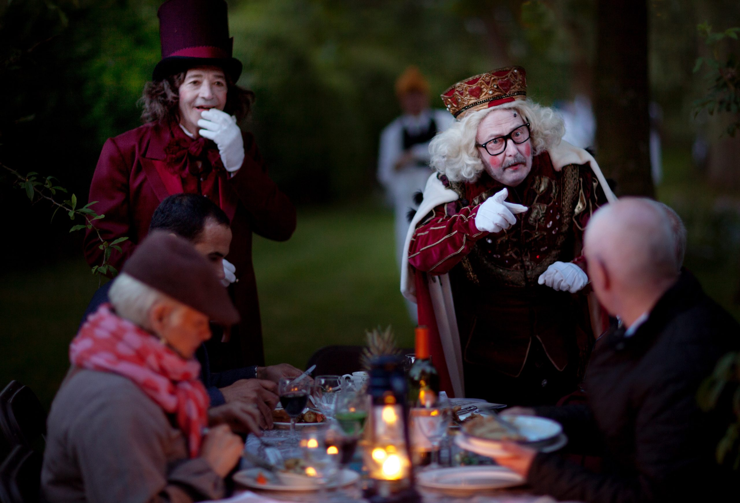 People sat a dining table are looking at a man pointing at one of the people seated. He is dressed as a King with a crown, a white painted face and pink circles on his cheeks