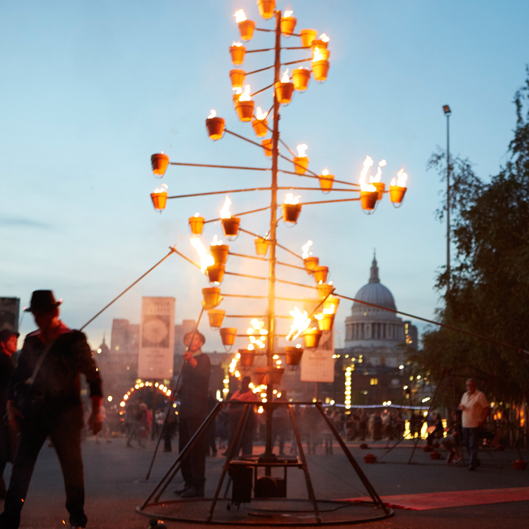 a Helix shaped structure with a small pot lit up into a flame at each end of the helix form
