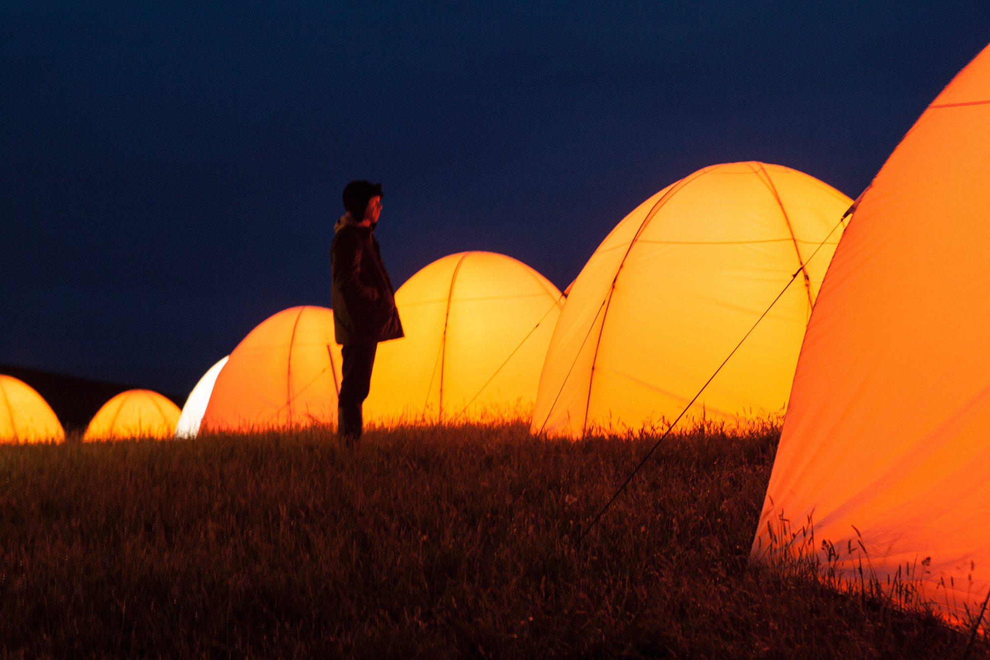 Boy standing in front of glowing tent in the dark