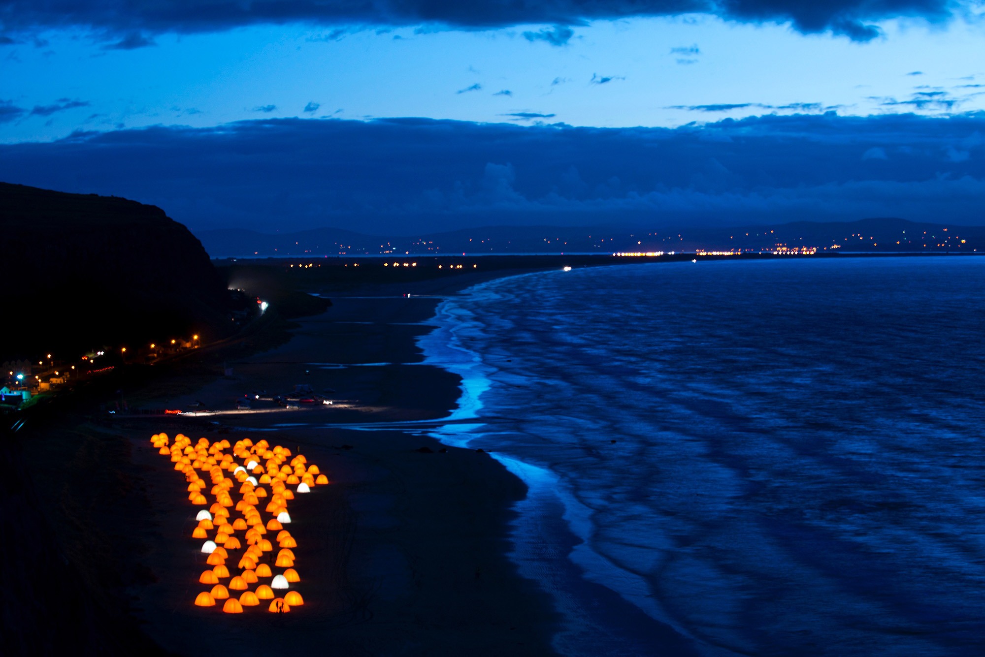 Aerial shot of peace camp tents glowing at dusk by the seafront