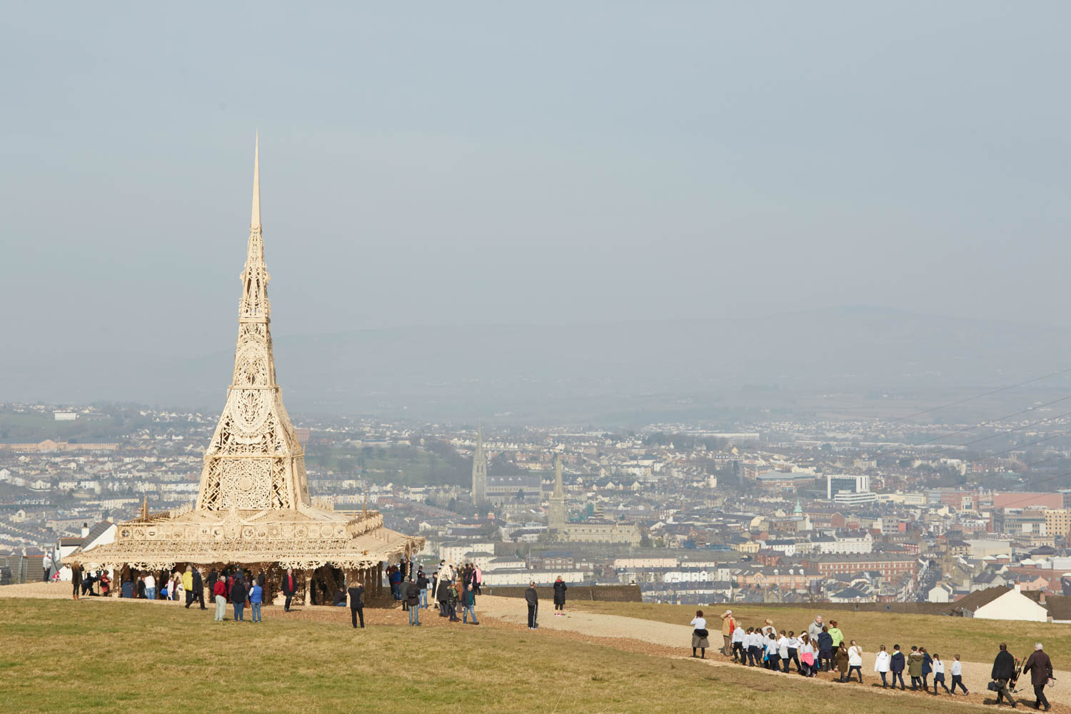 View of the people walking around Temple in the day on a hill with Derry~Londonderry visible in the background