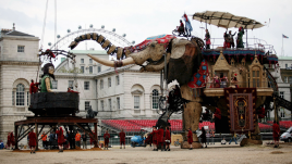Side view of giant elephant puppet facing giant girl puppet sitting in a black bowl. Part of the London Eye is visible from in the background