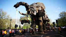 Giant puppet The Sultan's Elephant picking up a yellow pick up truck with its trunk with a crowd around it.