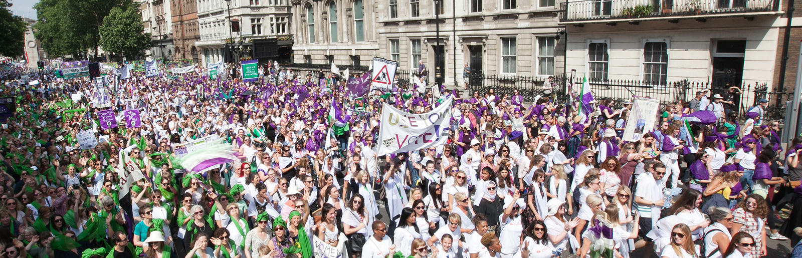 Crowd of women dressed in purple, white and green holding up banners