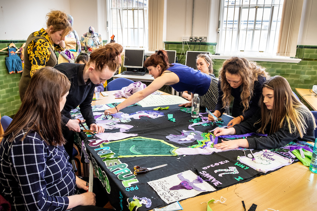 Women sitting around a table collaboratively crafting and sewing a banner.