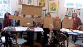 Ten women are standing holding cardboard squares with empowering slogans written on them like
