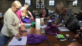 Women in a church standing around a table and working together to sew pieces of brightly coloured material. They look happy and engaged in the task.