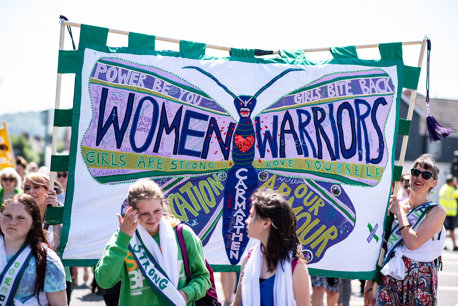 Women holding up Green and purple banner with a purple butterfly in the centre. On the banner is written WOMEN WARRIORS and other inspiration phrases