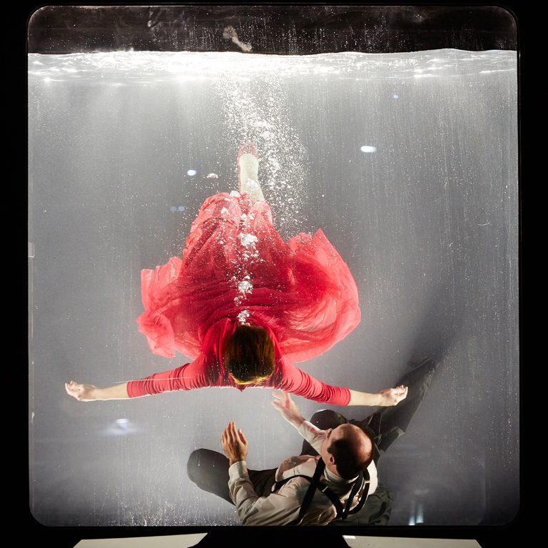 Woman in a red dress and man in a suit in a clear cube tank filled with water
