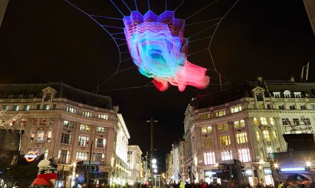 Colourful floating sculpture above the bright lights of Regent Street in London.