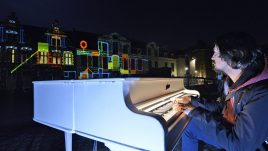 Man playing piano in foreground and light installation illuminating a building.
