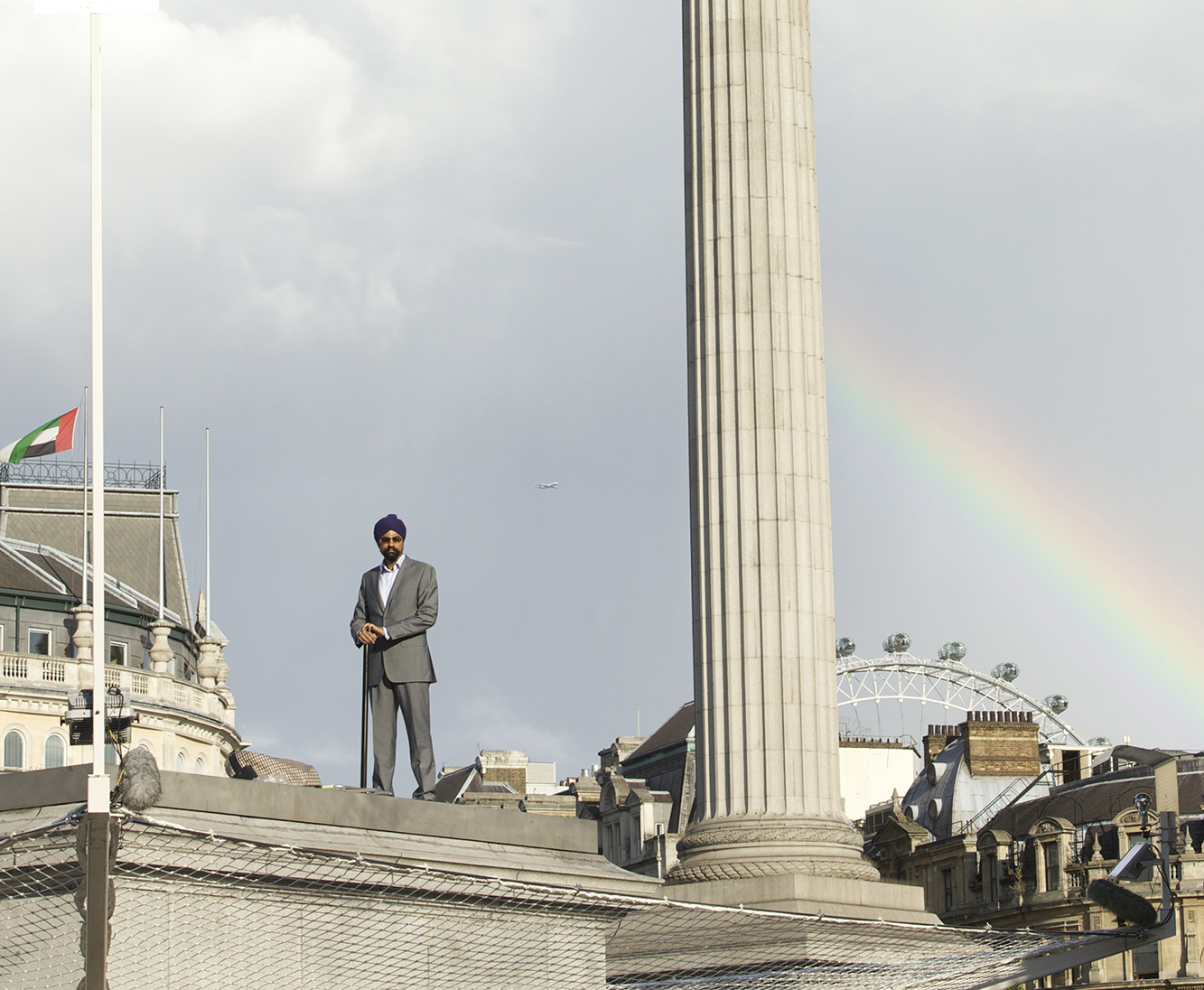 Man standing atop the plinth with a rainbow in the background