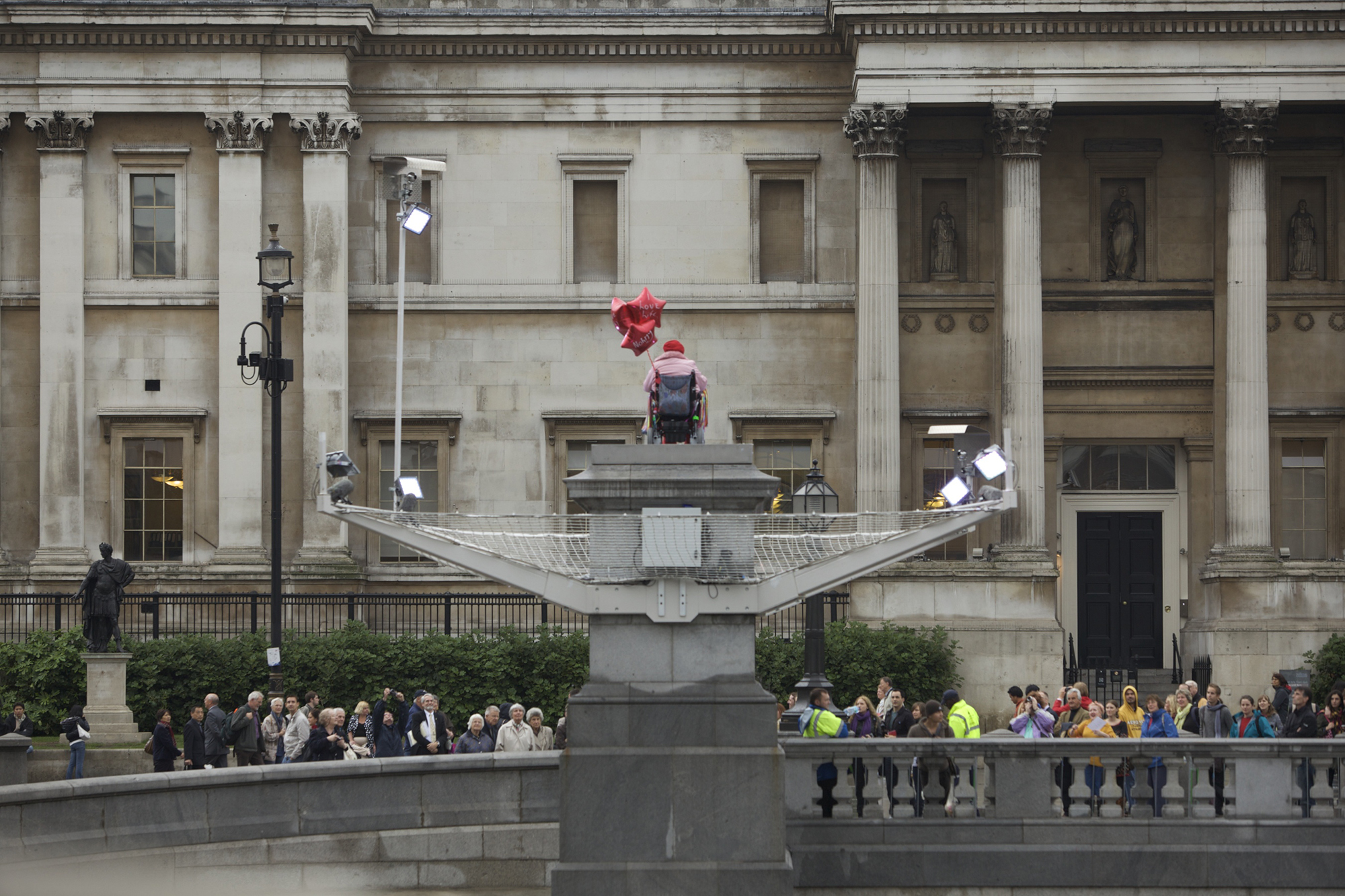 Woman with heart shaped balloon in wheel chair on the Fourth Plinth.