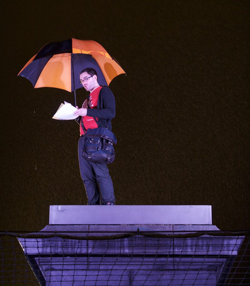Man holding a black and red umbrella reading from sheets of paper while standing on the fourth plinth for One & Other