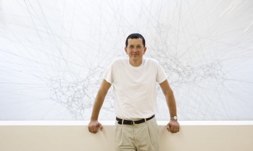 Landscape image of Antony Gormley against white backdrop