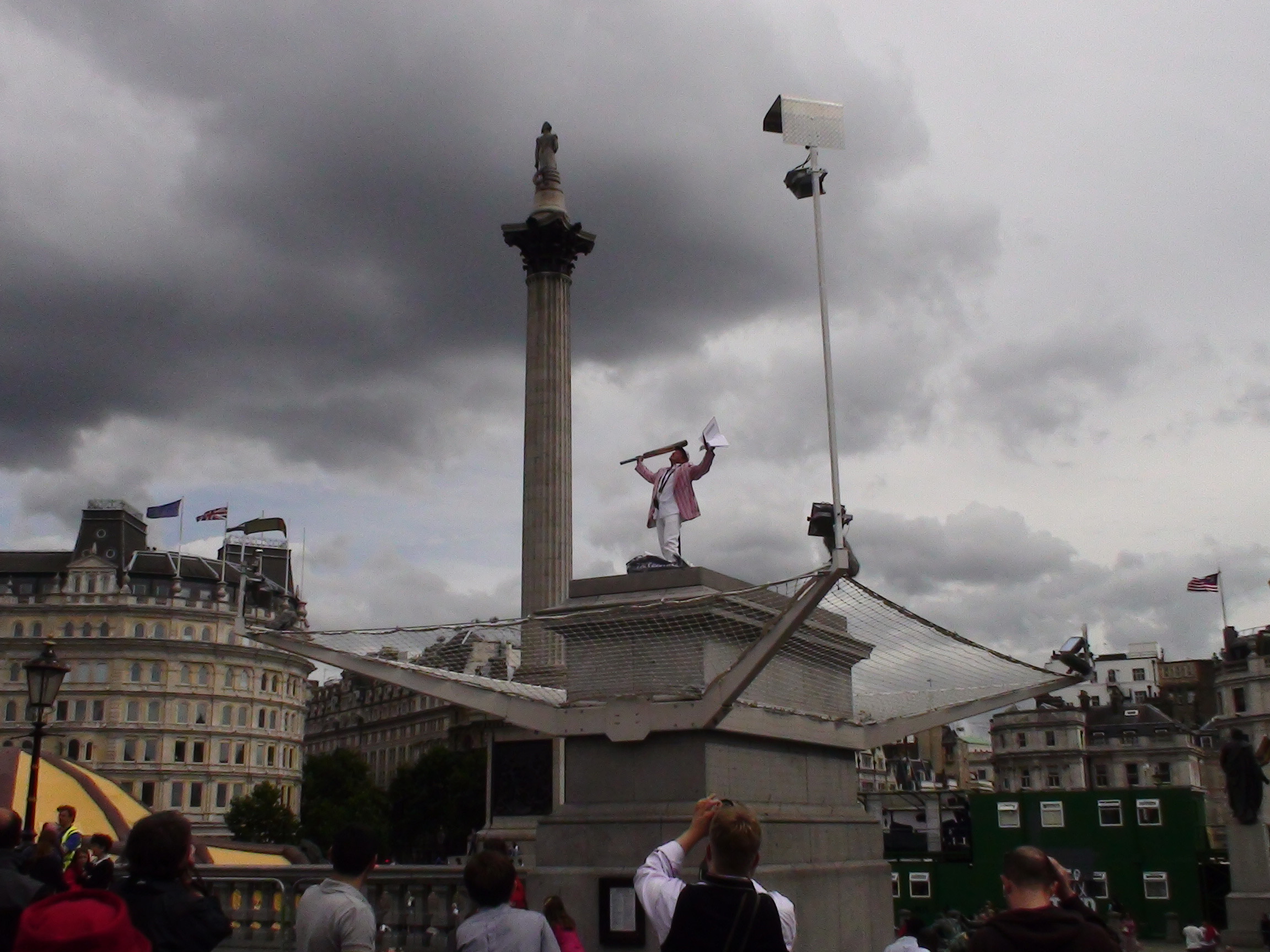 Man in top that waving a flag on top of the Fourth Plinth.