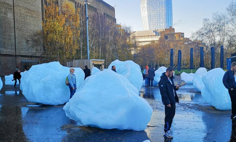 People around giant glacial ice blocks outside of the tate modern