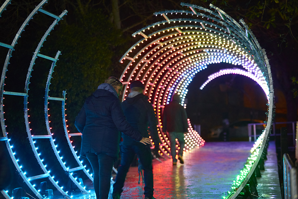 3 people watching through a rainbow light tunnel
