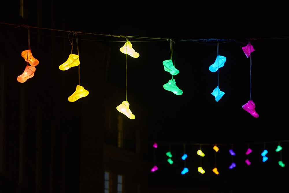 Multicolours shoes hanging in strings across the path