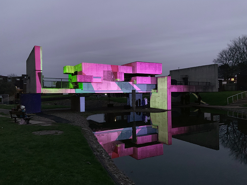 Geometric structure illuminated in pink and green light.