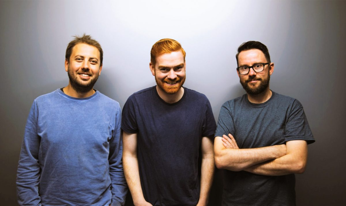 Three men standing against a grey background