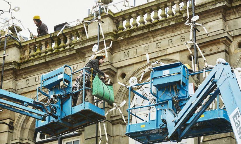 Men in cherry pickers installing the light work Key Frames on Durham Miner's Hall