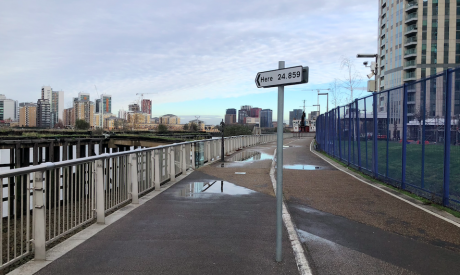 A walkway by the River Thames with a traffic sign planted in the middle, the sign is pointed in the direction of the river on it is written