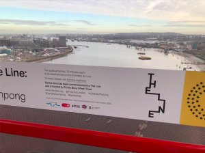 View of the river thames from the emirates sky line. Inside the carriageway is a sign which reads