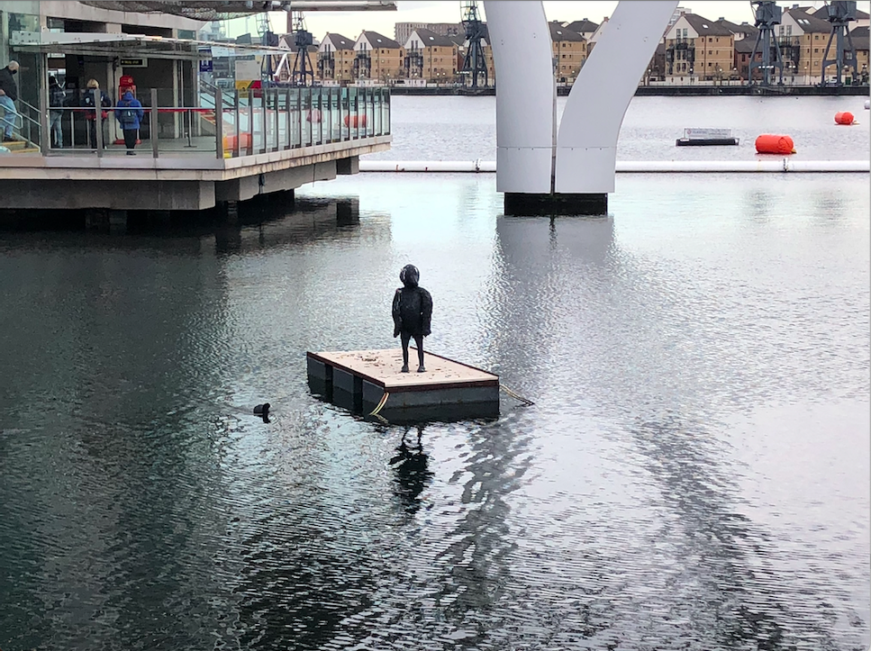 In the middle of the river, on a floating wooden square is a sculpture of the silhouette of a young boy with the face of a bird