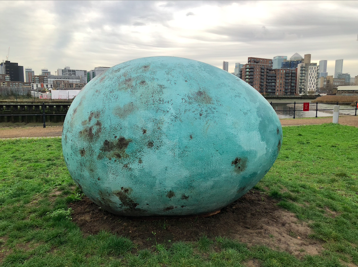 Lying on the grass, a giant egg that is a rusted turquoise colour