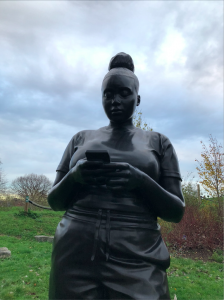 Close up shot of the bronze sculpture, a black woman looking down at her phone