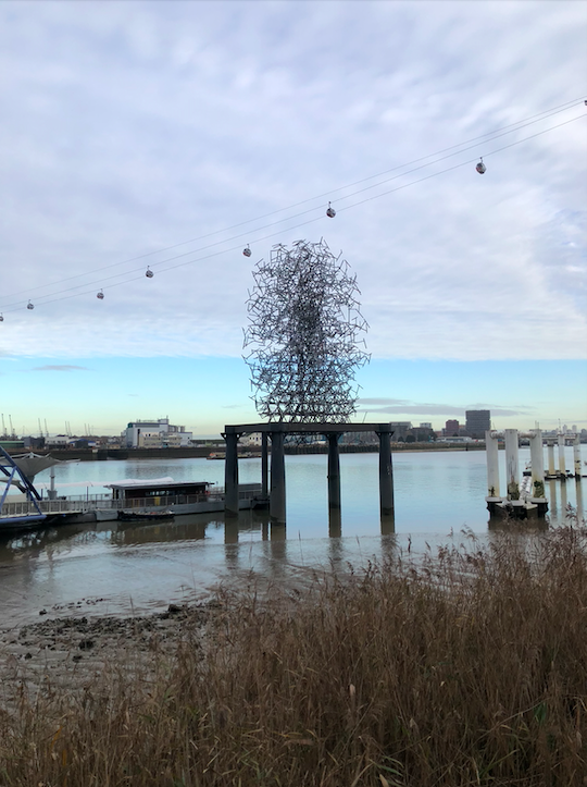 By the pier above the river, the piece is on a plinth which appears like a large table. The sculpture is made of metal and from a distance looks like a ball of energy made from several straight lines coming outwards into the shape of an egg