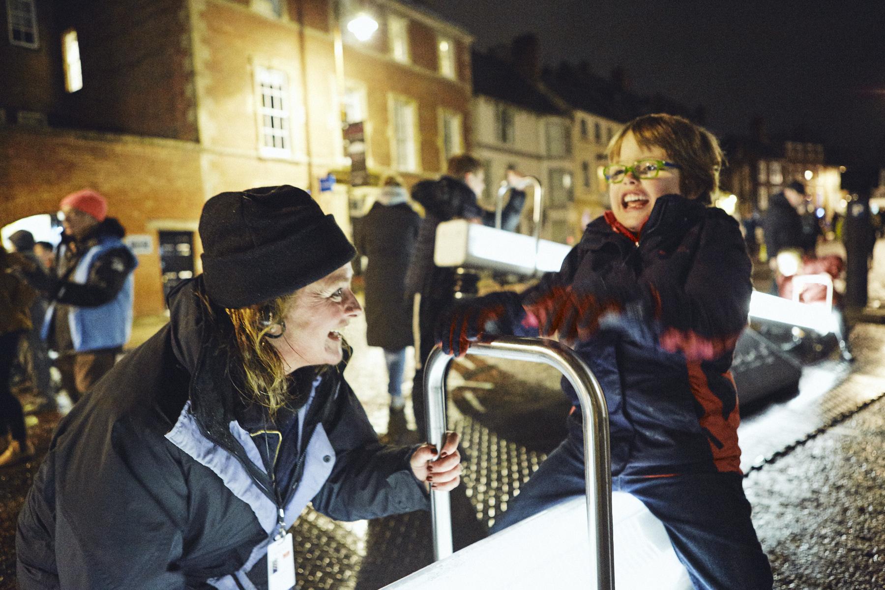 Kate Harvey interacting with illuminated seesaws