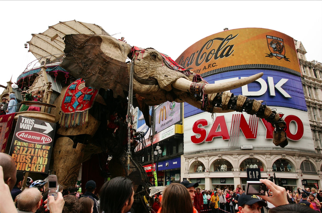 A below view of a giant puppet elephant in front of advertising signage with a large crowd around it.