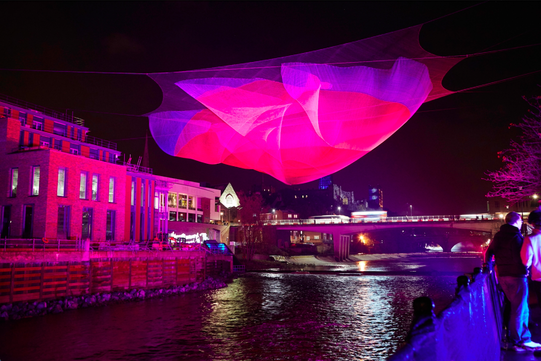 A layered net hung about the River. The net is projected with purple and pink colours.