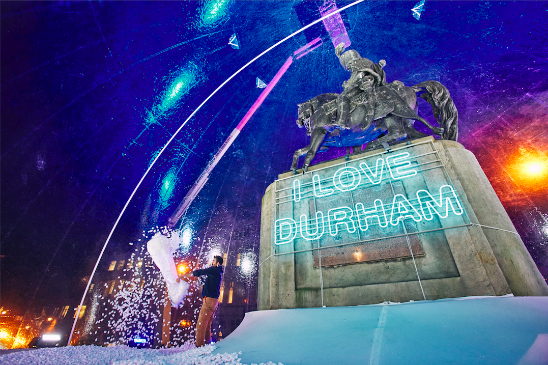 Man inside the snowglobe, empty a large bag with the fake snow onto the ground. Behind him is the statue of a man riding a horse on a plinth with the illuminated words I LOVE DURHAM on it.