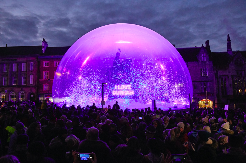A large crowd gathered around a snow globe, in the snow globe is glitter and at the centre is a statue of a man riding a horse on a plinth with the illuminated words I LOVE DURHAM on it.