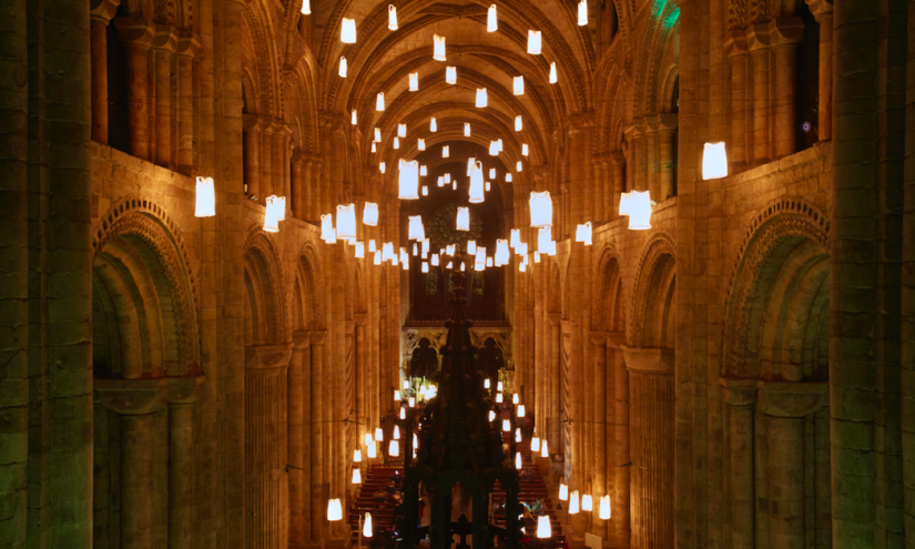 Glowing lanterns floating in the centre of a cathedral