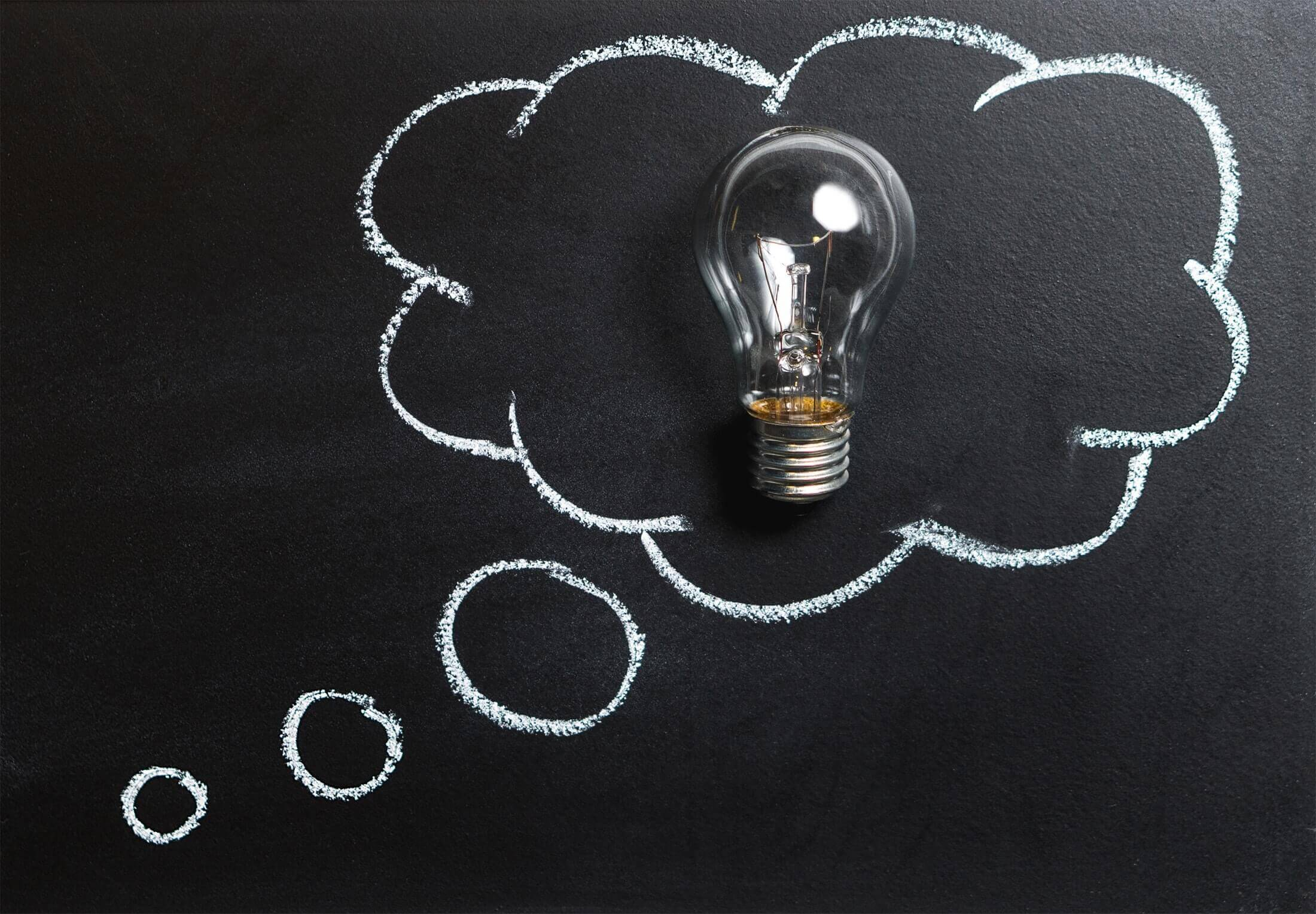 Light bulb on a blackboard with a thinking bubble drawn around it.