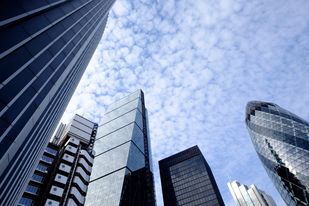 Upward view of sky scrapers office blocks in a central city with blue sky and light cloud behind