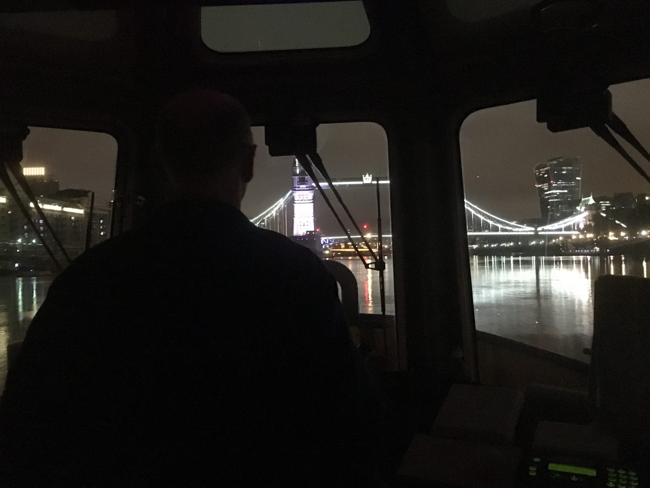 Dark view out onto the Thames from behind the wheel of a boat.