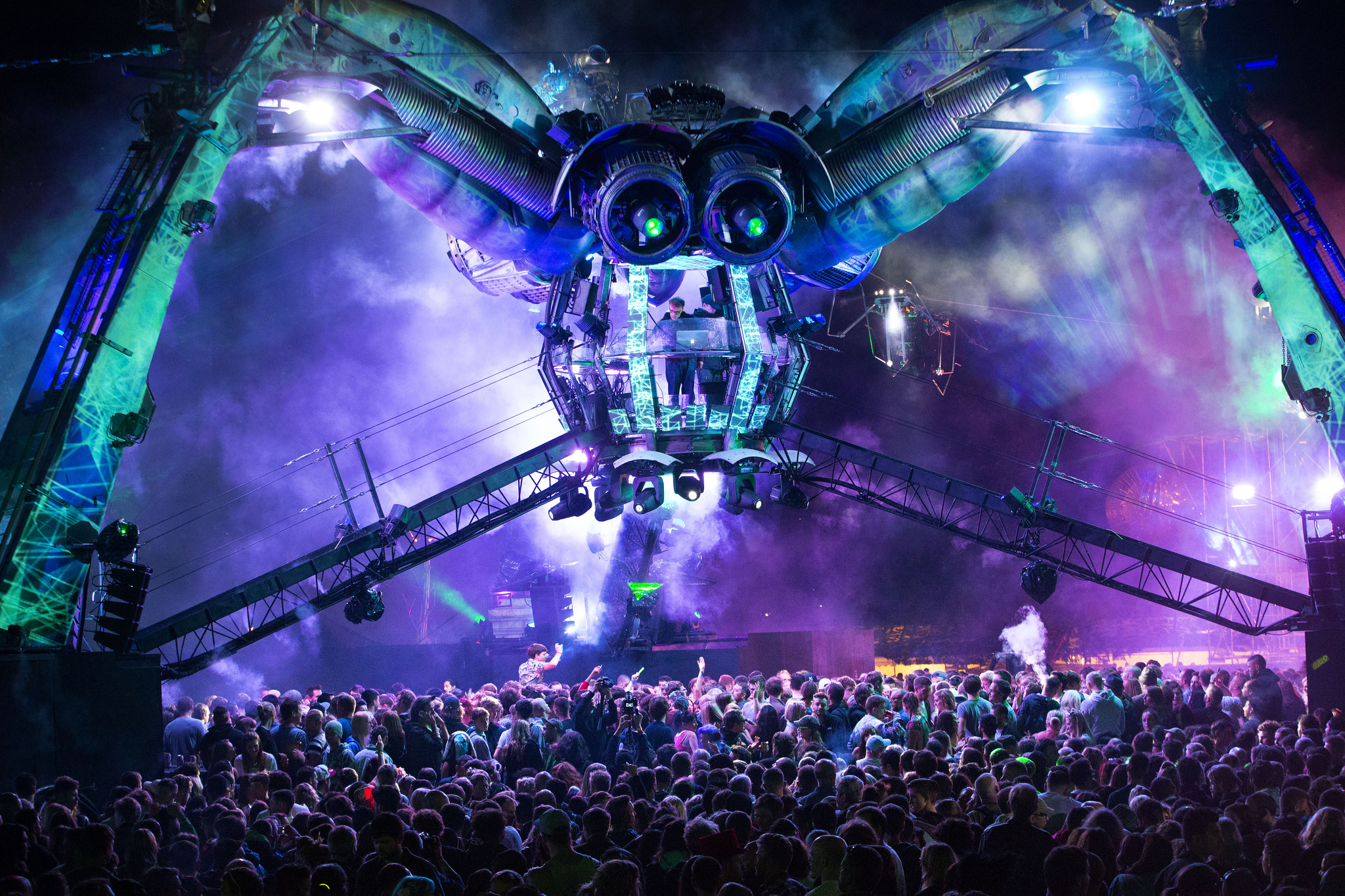 Purple mechanical spider in a crowd of people