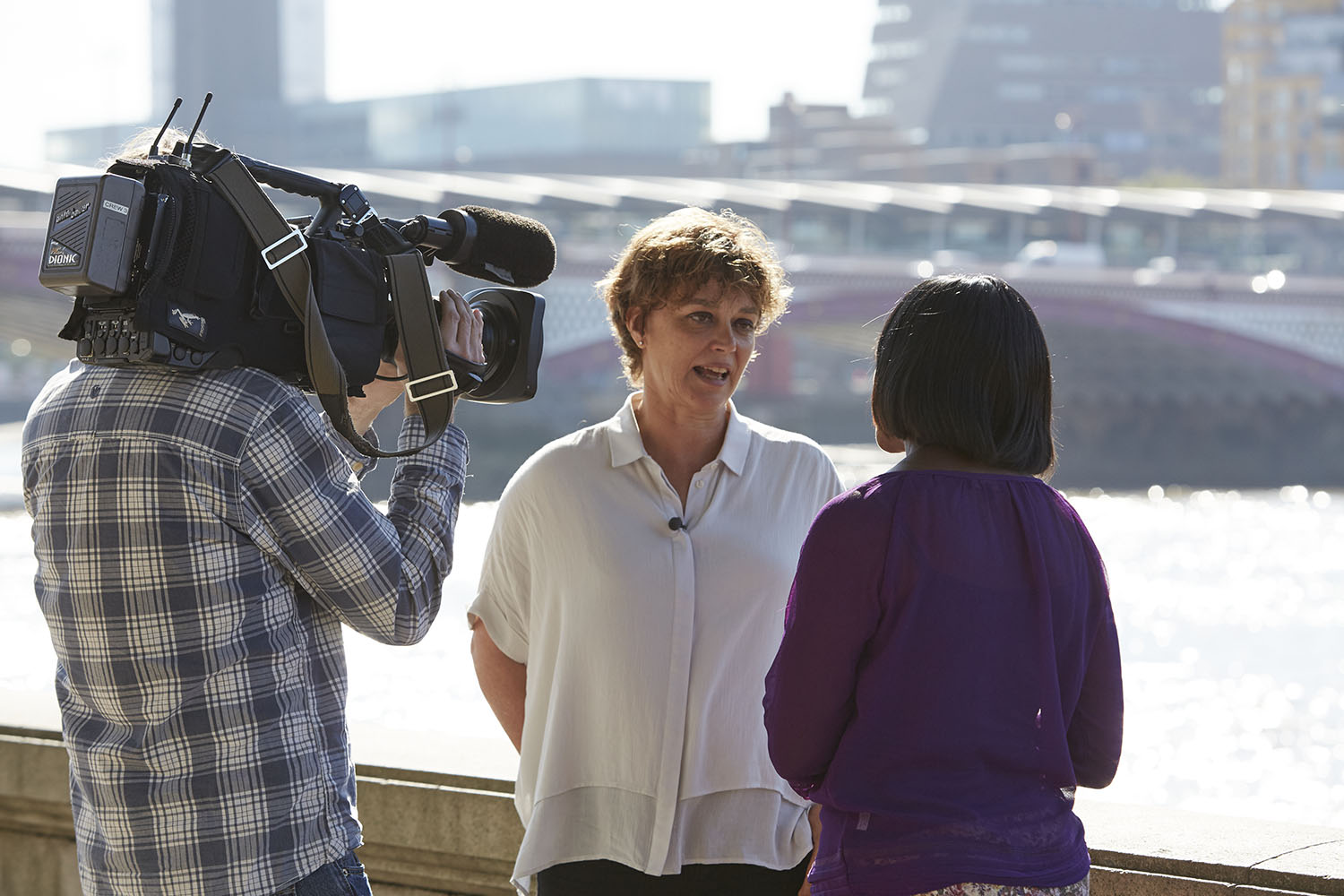 Artichoke's Director, Helen Marriage wearing a white shirt and being interviewed on camera by a woman with dark hair in a purple top