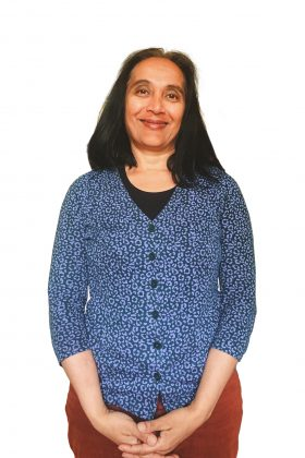 Headshot of Daksha smiling and wearing a blue cardigan, black top and red trousers